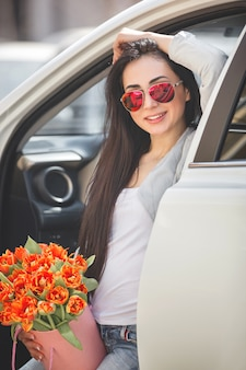 Very beautiful woman in the car holding flowers