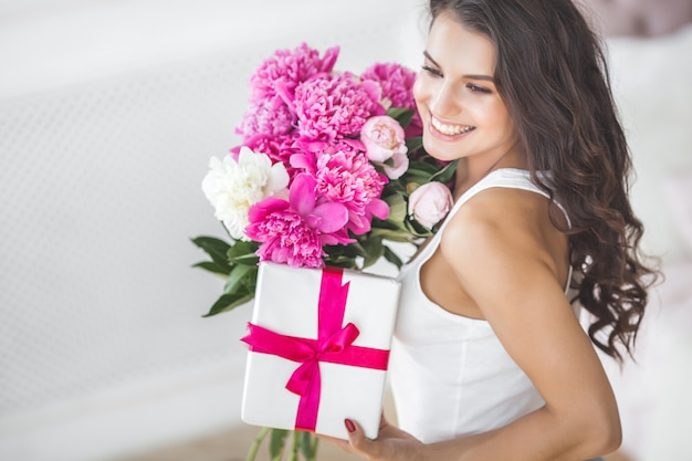 Very beautiful woman with flowers and gift indoors