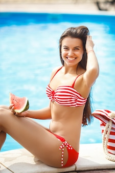 Very beautiful woman with watermelon in the pool