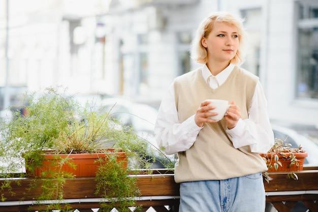 Очень красивая молодая женщина в кафе и пьет кофе или чай, вид на улицу