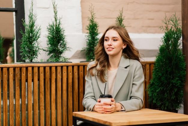 Очень красивая молодая женщина, сидеть в кафе и пить кофе или чай с круассаном, вид на улицу