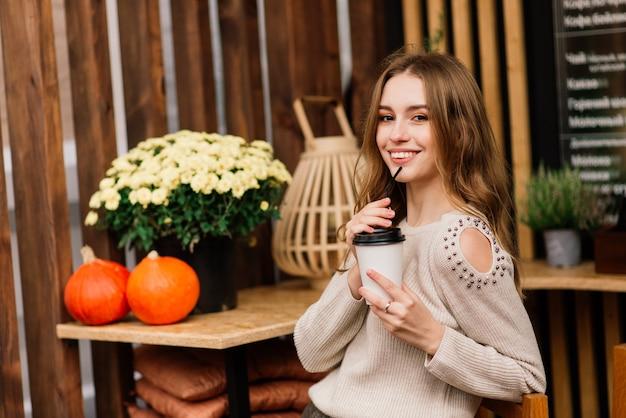 Очень красивая молодая женщина, сидеть в кафе и пить кофе или чай с круассаном