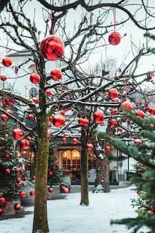 매우 아름답게 장식 된 크리스마스 트리는 많은 수의 큰 밝은 빨간색 공, 잘츠부르크, 오스트리아.