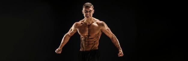 Очень мускулистый парень, бодибилдер позирует. красивый спортивный парень мужской силы. фитнес мускулистый мужчина.