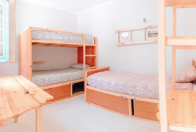 여러 개의 침대와 이층 침대가있는 매우 밝은 호텔 객실