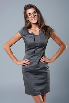 Очень очаровательная молодая бизнесвумен, одетая в элегантное платье