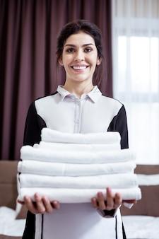 非常にきれいな。白いタオルを持ってあなたを見ている喜んでうれしそうなメイド Premium写真