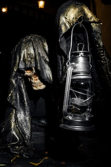 A very creepy skeleton that holds a lamp in his hand