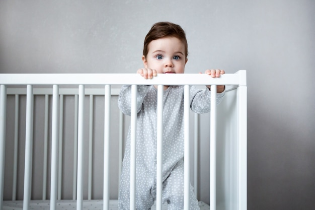 Very cute baby boy smiles standing in the crib in white room side view