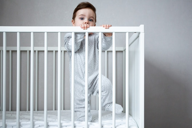 Very cute baby boy smiles standing in the crib in white room side view.