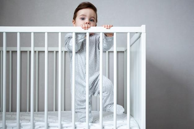 아주 귀여운 아기 소년 화이트 룸 측면보기에서 침대에 서 미소.