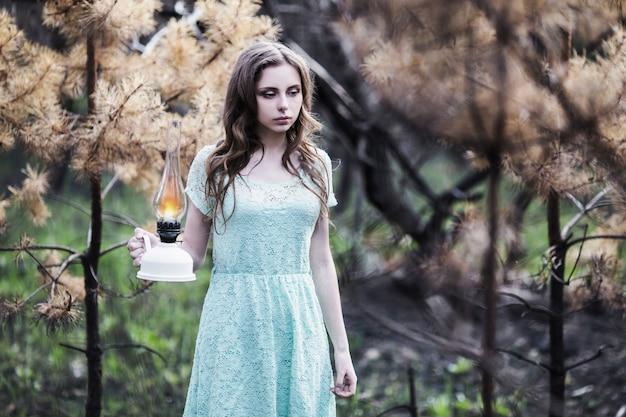 등유 램프와 아주 귀여운 어린 소녀. 인형 모양. 자연에 청록색 드레스에 갈색 머리를 가진 여자. 긴 머리. 자연광. 성격에 포즈 모델. 손에 램프. 숲에서 길을 잃었다