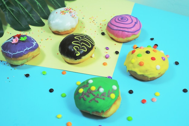 Very delicious rainbow donuts on a colorful background