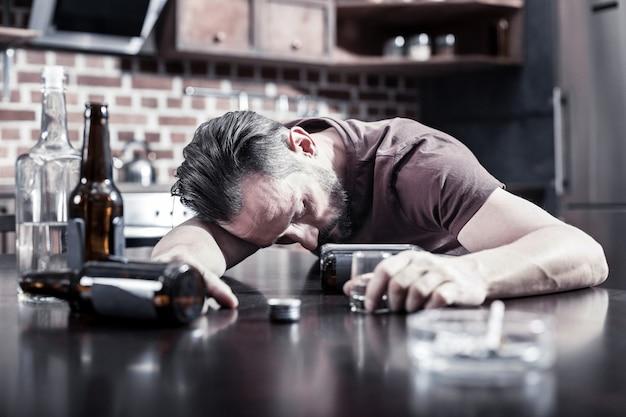 아주 취 했어. 불행한 피곤한 수염 난 남자가 테이블에 앉아 매우 취한 상태에서 자고