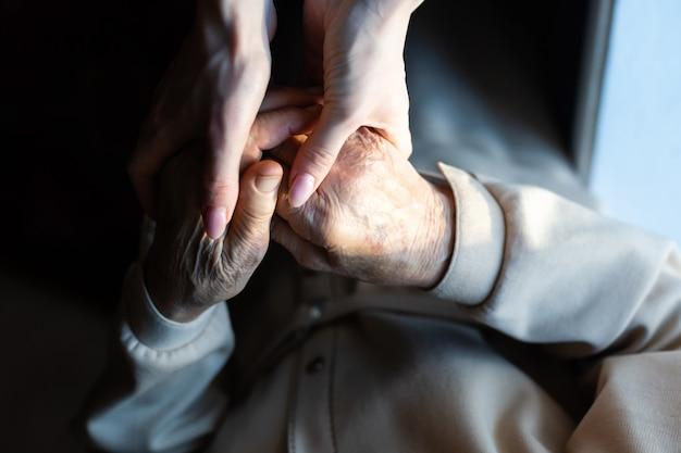 Очень пожилые прабабушка и внучка держатся за руки Premium Фотографии