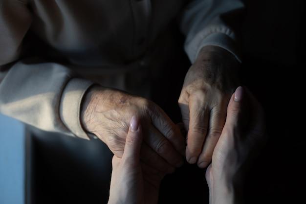 Очень пожилые прабабушка и внучка держатся за руки