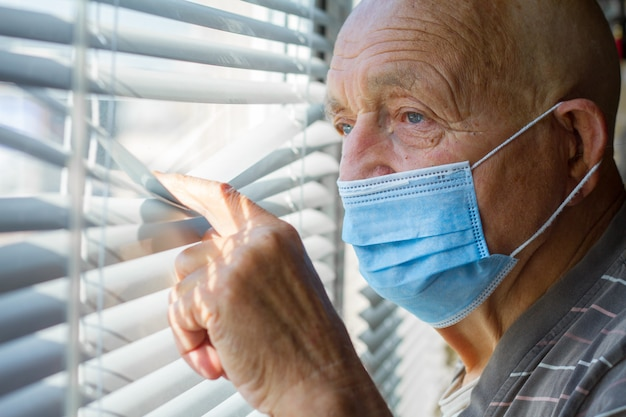 Very elderly man in blue protective mask on his face looks out through the window, stay at home concept