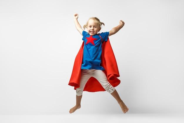 白い壁に沿ってジャンプするヒーローのような格好をした非常に興奮した少女。