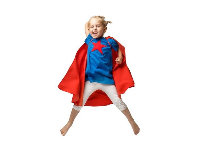 白い背景で隔離のヒーロージャンプのような格好をした非常に興奮した少女。