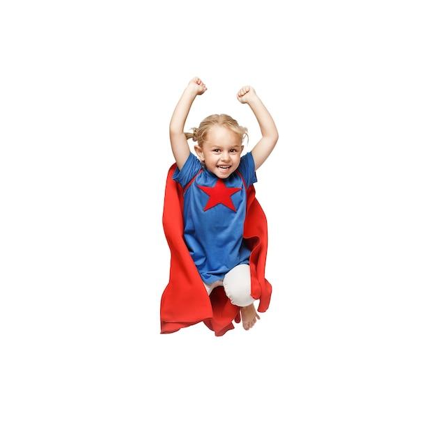 非常に興奮した少女は、白い背景で隔離のヒーロージャンプのような格好をしています。