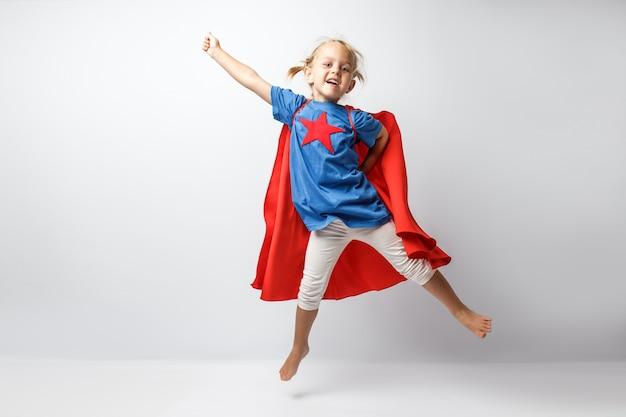 白い壁に沿ってジャンプするスーパーヒーローのような格好をした非常に興奮した少女。