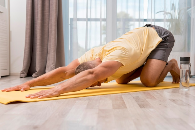 Very fit man exercising at home on mat with water bottle