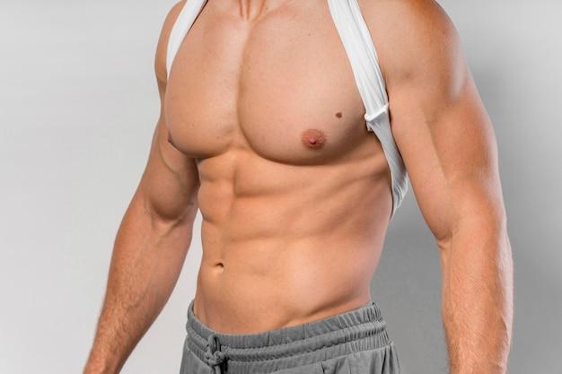 Очень подтянутый мужчина позирует без рубашки