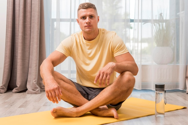 Very fit man working out at home on mat with water bottle