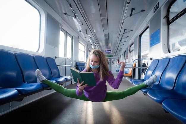 体操の分割に座っている地下鉄の車で本を読んで非常に柔軟な身に着けているマスクの女性。健康的なライフスタイル、柔軟性、ヨガの概念