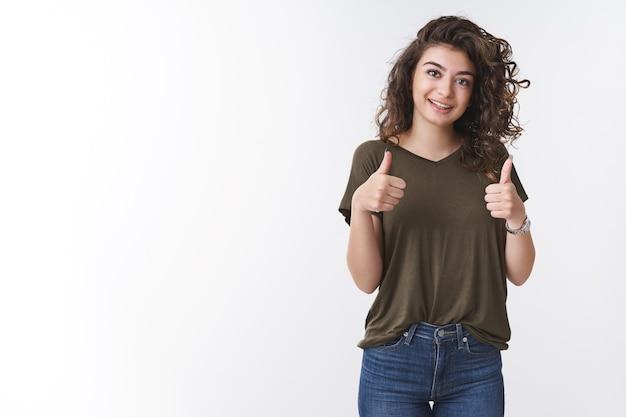 とても良い。陽気な支持的なかわいいアルメニアのガールフレンドの縮れ毛のショーの親指は、友達が元気に笑うことを奨励します広く肯定的な返信はあなたのアイデアのように同意し、白い背景に立っています