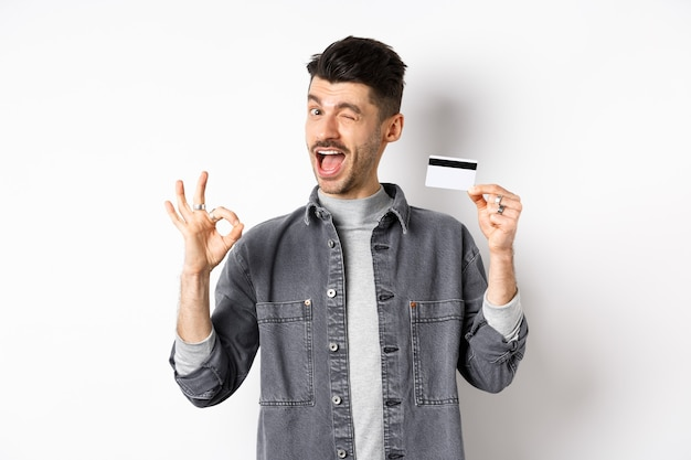 Very good. smiling guy with plastic credit card showing okay sign, smiling and winking satisfied, recommend bank, standing on white background.