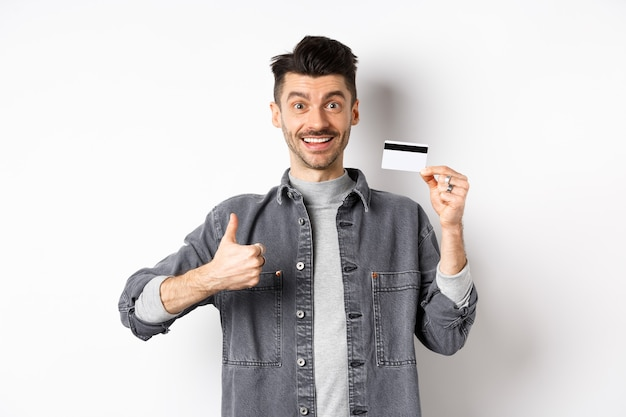 Very good. smiling guy with plastic credit card showing thumbs up, smiling satisfied, recommend bank, standing on white background.