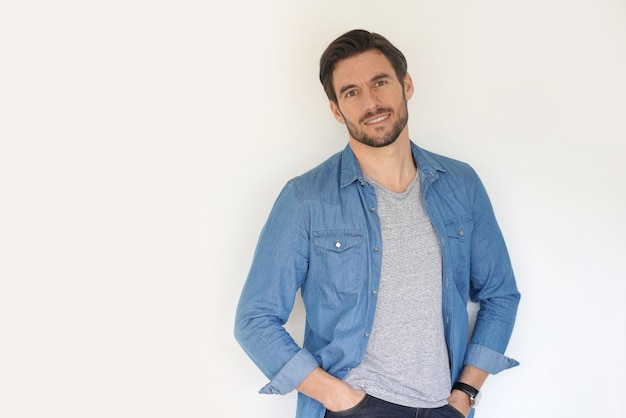 Very handsome casual man smiling and standing with hands in pocket