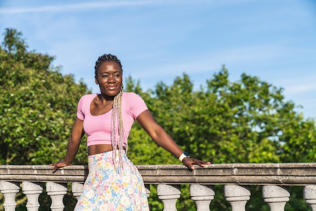 青い空と晴れた日に公共公園の石の手すりに寄りかかって笑っている非常に幸せな黒人アフリカの女性。黒人ファッション女性のライフスタイル