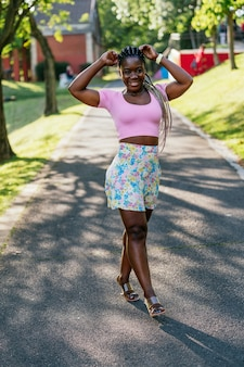 Very happy black african woman smiling and walking in a public park. lifestyle of black fashion woman