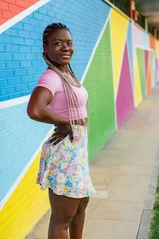 多くの色の壁の上を歩いてポーズをとって非常に幸せな黒人のアフリカの女性。幸せなアフリカの女性のライフスタイルの写真