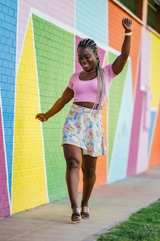 Very happy black african woman walking and posing on a wall of many colors. lifetyle photo of a happy african woman