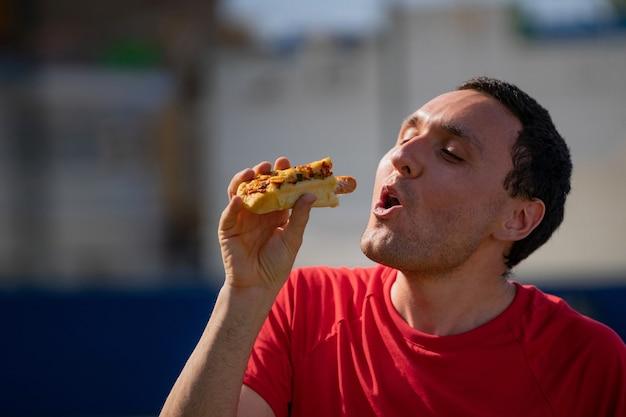 Very happy boy eating a hot dog