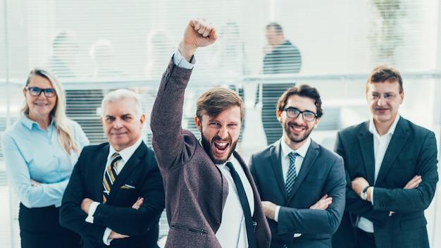 그의 비즈니스 팀 앞에 서있는 아주 행복 한 사업가