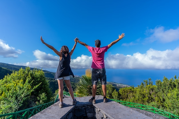 A very happy couple on top of the mountain at the viewpoint of the cubo de la galga