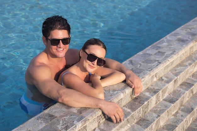 サングラスをかけているとても幸せなカップルは、プールでお互いを楽しんでいます。手に女性を保持している男性