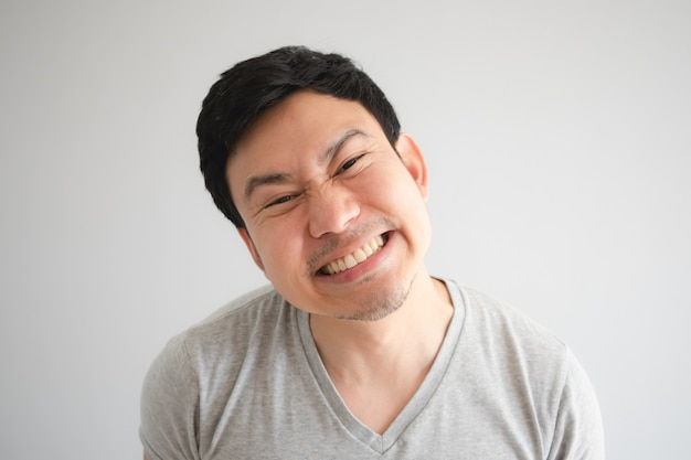 Very happy funny face of man with a big innocent smile in grey t-shirt