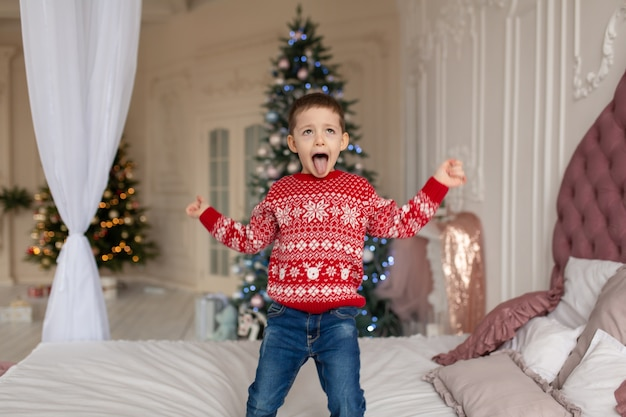 Very happy little boy in red knitted sweater jumping on the bed. christmas tree background