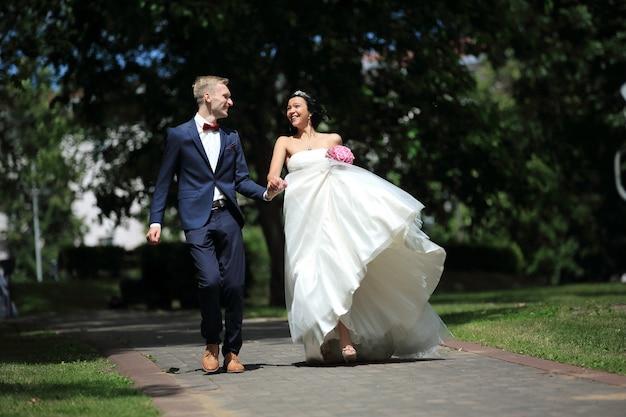 Очень счастливая пара молодоженов гуляет по парку в день свадьбы
