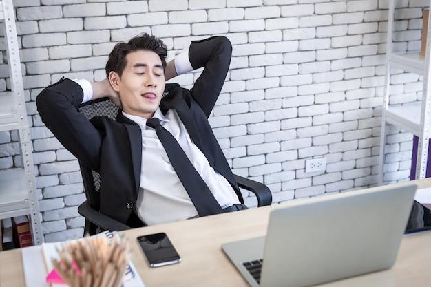 노트북 컴퓨터, 스마트폰, 연필로 노트북에 있는 성공적인 아시아 젊은 사업가의 매우 행복합니다.