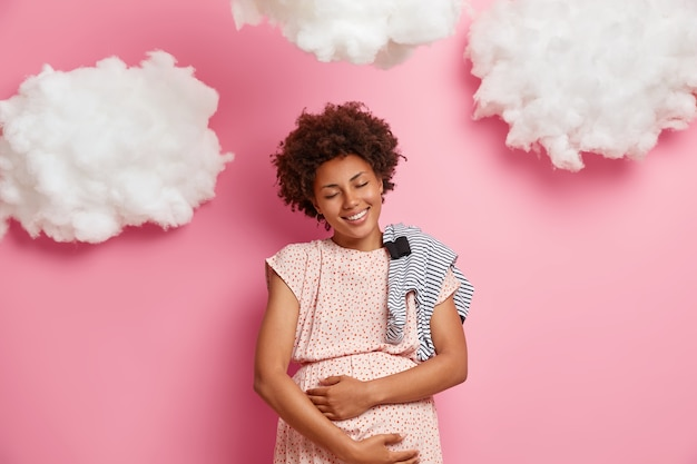 Very happy smiling african american pregnant woman touches belly gently and feels her baby, buys romper for newborn, enjoys moment of maternity and motherhood, plays with precious future unborn child