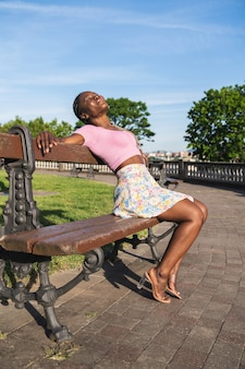 Very happy smiling black african woman sitting on a bench in a public park on a sunny day with blue sky. lifestyle of black fashion woman