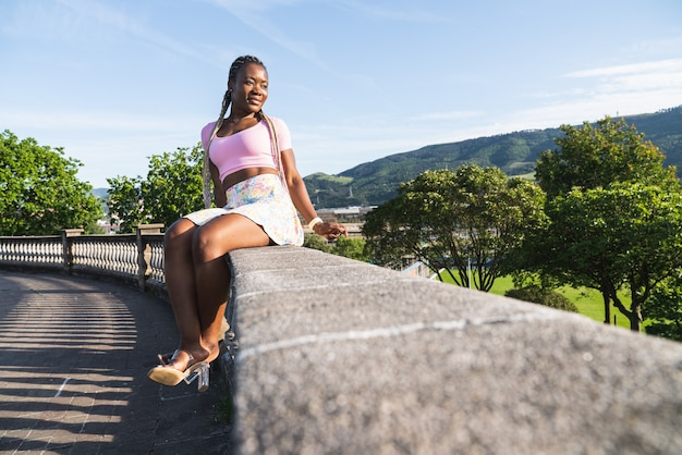 Very happy smiling black african woman sitting on a gazebo in a public park on a sunny day with blue sky. lifestyle of black fashion woman