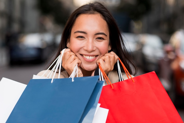 販売アイテムの買い物袋を保持している非常に幸せな女