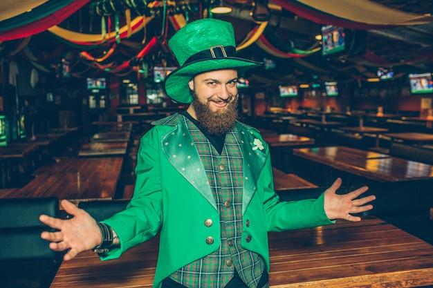 緑のスーツを着た非常に幸せな若い男がパブに立ってポーズします。彼は聖パトリックの衣装を着ています。